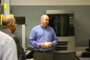 Penn State DuBois Assistant Professor of Materials Engineering Craig Stringer explains the functions of the 3-D printer to his left during the DCED tour of campus engineering facilities. (Provided photo)