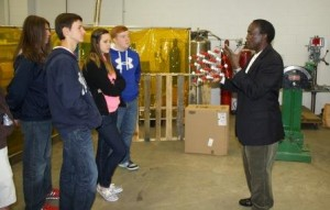 Professor of Engineering Daudi Waryoba explains the properties of powder metal samples to a group of high school students in one of the campus engineering labs. (Provided photo)