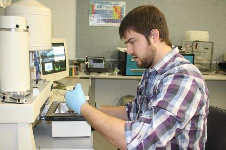 Nicholas Carrier examines samples of powder metal while running tests for his ongoing research project in a campus engineering lab. (Provided photo)