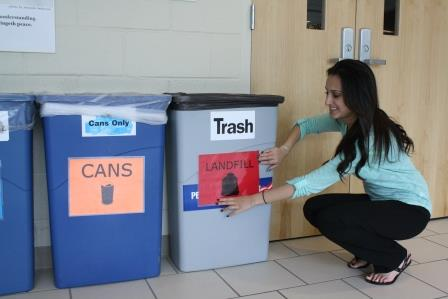 Student Rima Shah attaches signs to different types of waste receptacles on campus, identifying the kind of waste the container is intended to hold. (Provided photo)