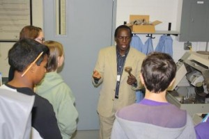 Penn State DuBois Assistant Professor of Engineering Daudi Waryoba explains the production process of powder metal parts used in the automotive industry during a Manufacturing Day presentation. (Provided photo)