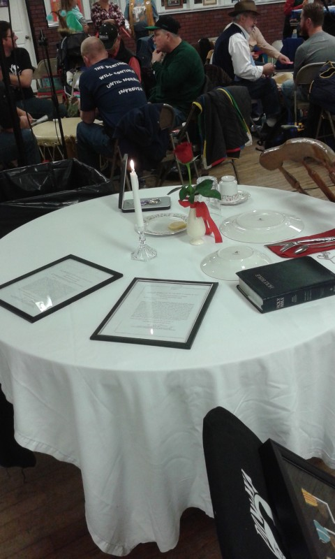 The POW/MIA table stands on display during the 16th annual Veteran's Day Pow Wow, held Saturday and Sunday at the Expo II building at the Clearfield Driving Park. The white tablecloth draped over the table represents the purity of their response to our country's call to arms. The empty chair depicts an unknown face, representing no specific Soldier, Sailor, Airman, or Marine, but all who are not here with us. The table itself is round to show that our concern for them is never ending. The Bible represents faith in a higher power and the pledge to our country, founded as one nation under God. The napkin stands for the emptiness these warriors have left in the hearts of their families and friends. A Purple Heart medal can be pinned to the napkin. The single red rose reminds us of their families and loved ones. The red ribbon represents the love of our country, which inspired them to answer the nation's call. The candle and its yellow ribbon symbolize the everlasting hope for a joyous reunion with those yet accounted for. The slices of lemon on the bread plate remind us of their bitter fate. The salt upon the bread plate represent the tears of their families. The wine glass, turned upside down, reminds us that our distinguished comrades cannot be with us to drink a toast or join in the festivities of the evening. (Photo by Kimberly Finnigan)