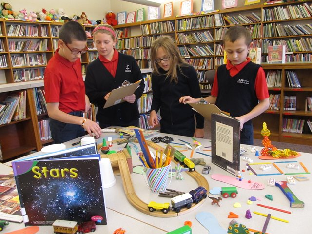 "Students survey the first of two ""I Spy"" investigation tables set up in the elementary library of DuBois Central Catholic as part of the school's ELO Program for third through fifth graders. (Provided photo)"